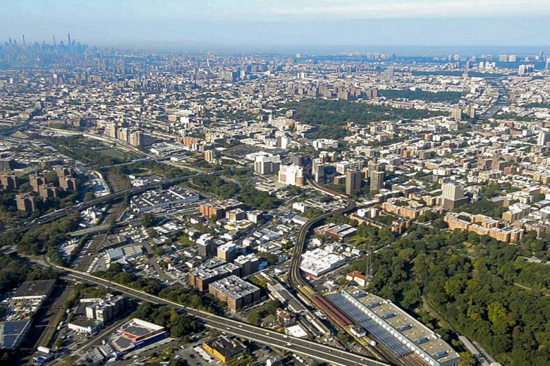 Aerial view looking down the Bronx River corridor as it flows through the South Bronx with distant views of Manhattan.
