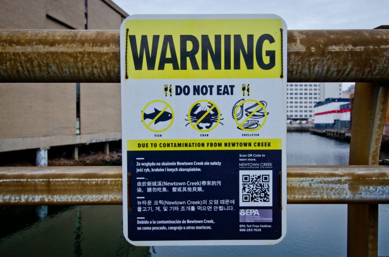 A sign warns people not to eat anything from Dutch Kills river in Long Island City due to pollution contamination from Newtown Creek.