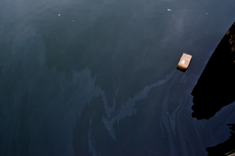 Oil contamination is visible on the surface of Dutch Kills river in the heavily industrialized area of Long Island City, New York.