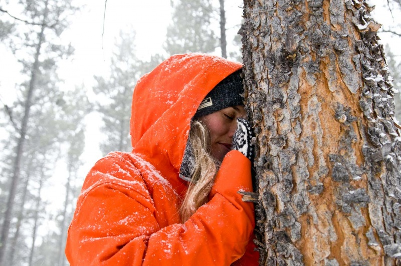 Pro snowboarder and environmentalist Chanelle Sladics pays homage to a lodgepole pine tree.