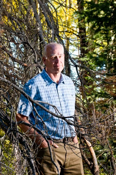 Colorado landscape photographer and environmental activist John Fielder stands with a lodgepole pine tree.