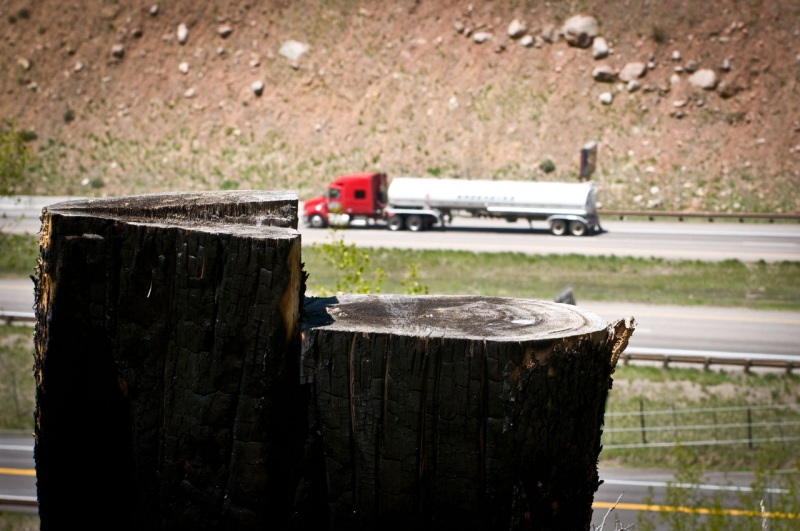 The stump of a charred lodgepole pine tree frames a gas truck on I-70 in Colorado.
