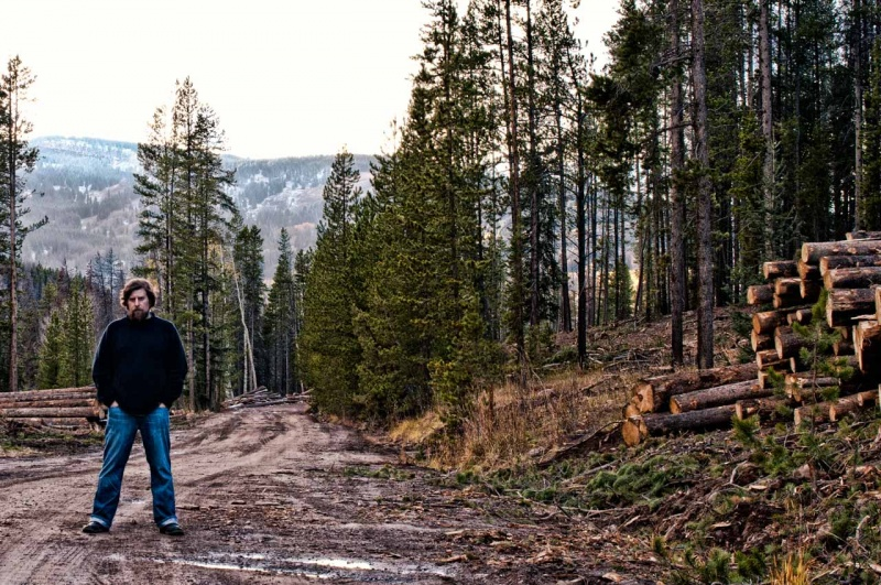 Conservation photographer Steven DeWitt stands on a logging road in a lodgepole pine forest removal project.