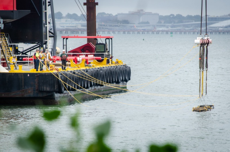 A crew lowers oyster gabions into the East River in New York City as part of the Billion Oyster Project oyster reef restoration in the Bronx.