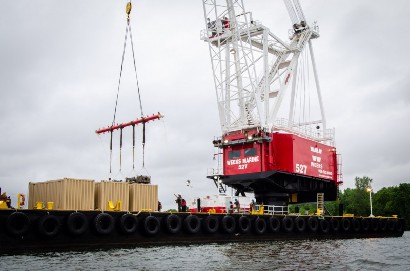 Oyster cages with live oysters loaded into shipping containers are being placed in the East River as part of a Billion Oyster Project oyster reef restoration in the Bronx.