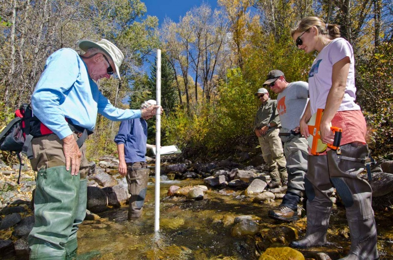 During a citizen scientist training session, local community members are shown how to measure stream pool depth on Two Elk Creek.